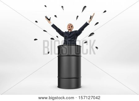 A businessman standing in an oil barrel with his arms up and oil drops around him on the white background. Oil and petroleum products. Black gold. Resource extraction.