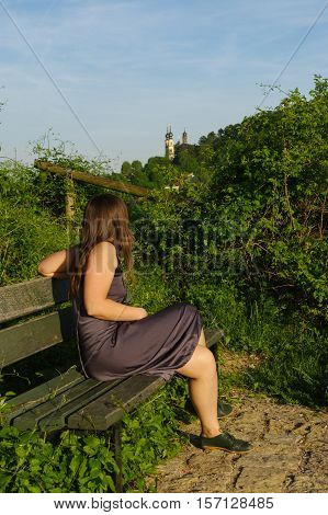 a happy girl relaxing on a bench with a view to grape field landcape and the Festung or fort Marienberg in background