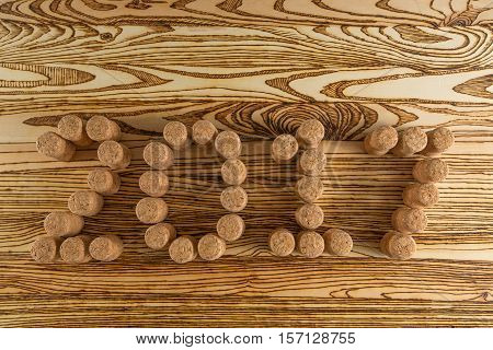 Inscription 2017 laid out champagne corks on wooden table for background.