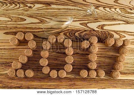 Inscription 2017 laid out champagne corks and an empty crystal glass on wooden table for background.