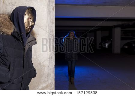 Criminal wearing a mask waiting for a woman. Robbery concept