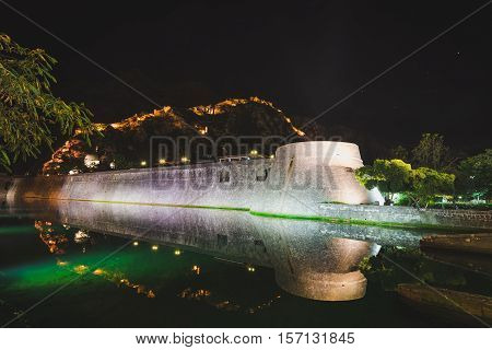 Kotor fortress wall and Old Town Stari Grad by night. Kotor castle San Giovanni and evening lights on surrounding wall reflected on the moat water. Unesco world heritage site in Montenegro.