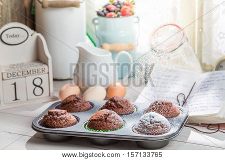 Decorating Tasty Cupcakes With Caster Sugar On Old Wooden Table