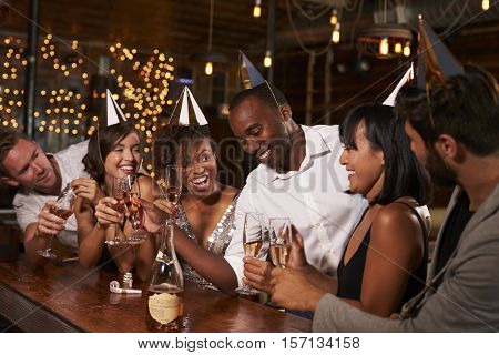 Friends in party hats celebrating New Year at party in a bar