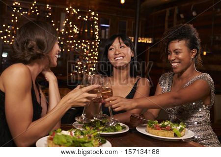 Three female friends make a toast over dinner at restaurant