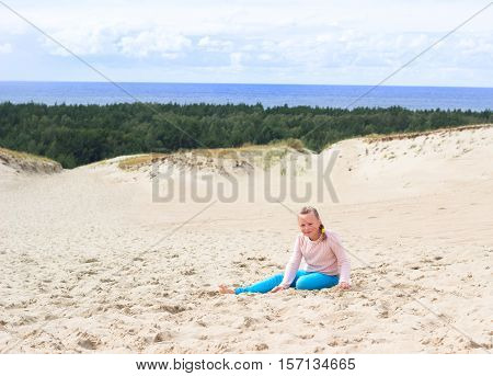 Happy little baby girl enjoys sand playing in the dunes on the beach