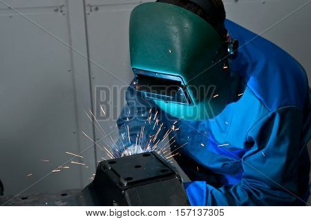 Welder working with electrode at semi-automatic arc welding.