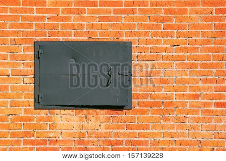 A fragment of a brick wall with a metal hatch closeup. Texture background