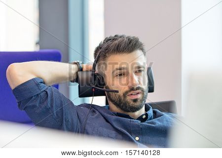 Mid adult businessman wearing telephone headset in office