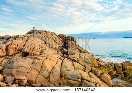 Woman climbing to the top of the rock at Port Elliot South Australia