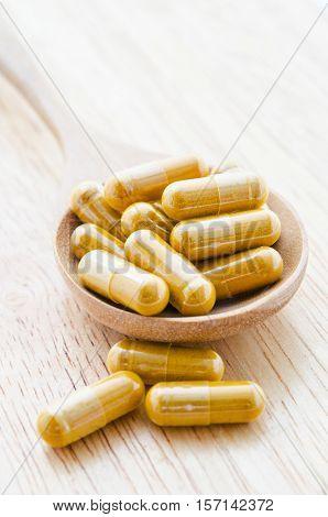 Alternative medicine tablets on a wooden spoon.