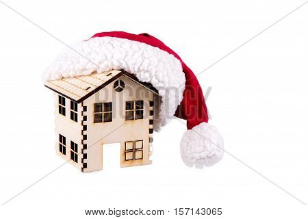House wooden a cap of Santa Claus isolated on white. Conceptual image.