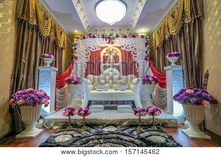 Bandar Seri Begawan,Brunei-Nov 10,2016:Colorful themed wedding stage with background of raised stage where the bride sits in a traditional Brunei wedding with colorful flower