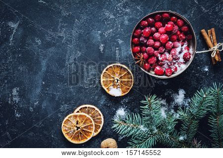 Christmas background, Winter background decoration: frozen cranberries, snow, frost, dried orange rings, fir tree and cinnamon sticks on dark background. Design mock up