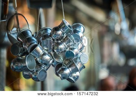 Groups of shiny metal ayran (Ayran - Traditional Turkish yogurt drink) drinking cups hanging in front of an old traditional store near Grand Bazaar. poster