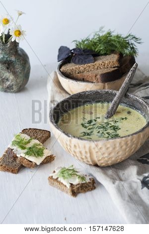 Cheese Soup With Mushrooms And Vegetables, Brown Bread With Butter, Dill And Basil On A White Wooden