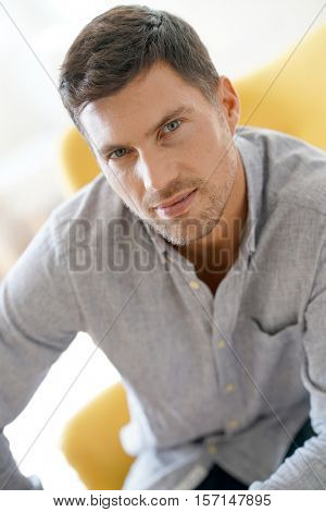 Handsome 40-year-old man sitting in armchair at home