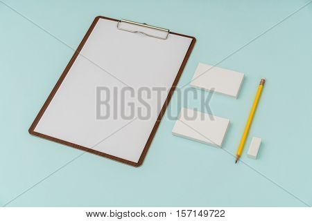 Clip board, paper,pencil  and business card on blue background