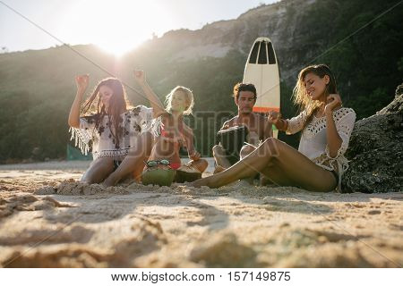 Happy friends enjoying vacation on the beach. Happy young people having fun at beach party women dancing and man playing dumbek.