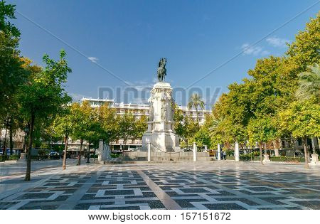 New Square, Plaza Nueva, with a monument to King Ferdinand III in the center, on a sunny summer day, Seville, Andalucia, Spain.