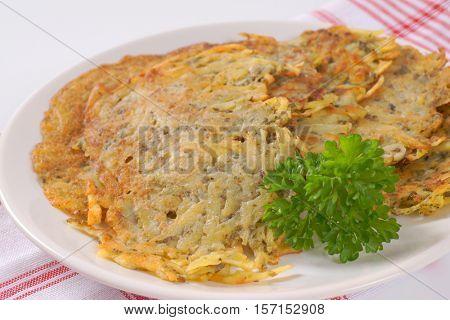 plate of freshly fried potato pancakes on checkered dishtowel - close up
