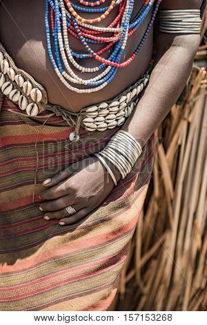 Hand of an Arbore woman with bracialet and metal rings.
