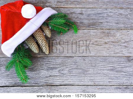 Christmas hat with Christmas tree branches and cones. Santa cap and fir-tree branch with cones on rustic wood. Christmas concept in horizontal layout.