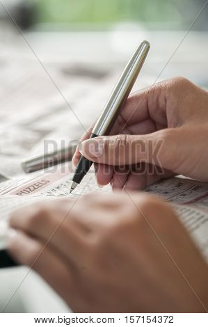 Crossword puzzle close-up. Hand of a young woman doing a crossword in a newspaper