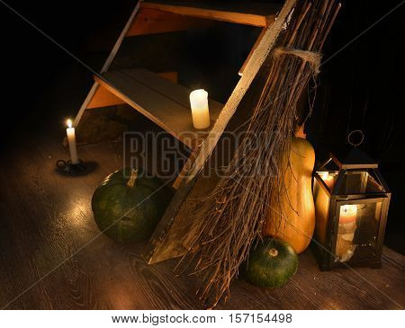 Scary mystic still life with staircase, candles, broom, pumpkins, lantern and magic objects in witch house. Occult or esoteric concept, Halloween background