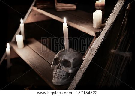 Mystic witchcraft ritual with scary skull and evil candles on wooden staircase. Occult or esoteric still life with magic objects, scary Halloween background