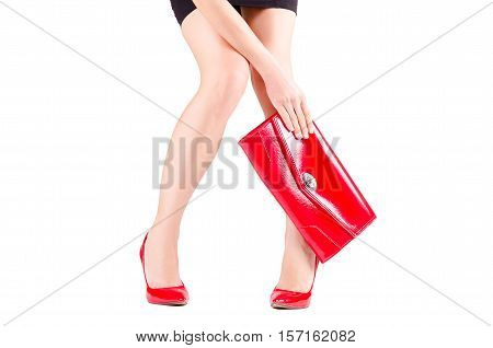 Slender beautiful female legs in red shoes and mini bag in hand isolated on white background
