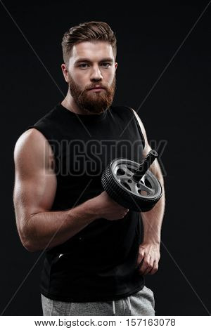 Cool athletic man with wheel. dide view. looking at camera. isolated dark backkground