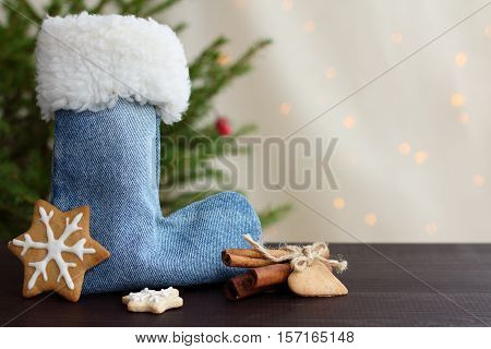 boot for gifts and cookies figure in the form of snowflakes under the Christmas tree against a background of holiday lights / Christmas surprises and mysteries