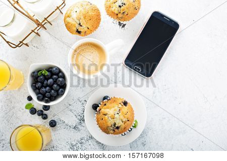 Bright and airy breakfast with blueberry muffin, big cup of coffee and smartphone overhead view with copyspace