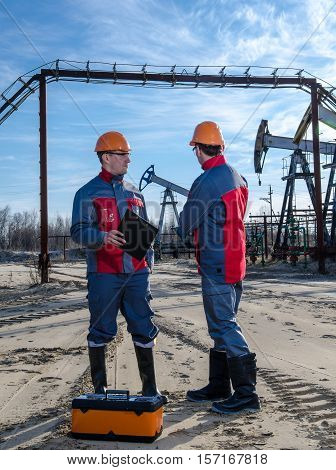 Two workers in the oilfield. Pump jack pipeline and wellhead background. Oil and gas concept.