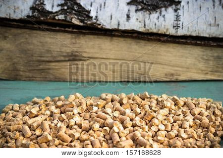 Wood Pellets And Firewood On A Green Background. Biofuels.