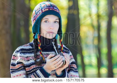 Young woman wearing knitted woolly hat and holding hot yerba mate drink container
