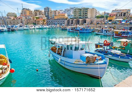 HERAKLION GREECE - OCTOBER 16 2013: The lazy fishing boats slowly ride on the waves in old harbor on October 16 in Heraklion.