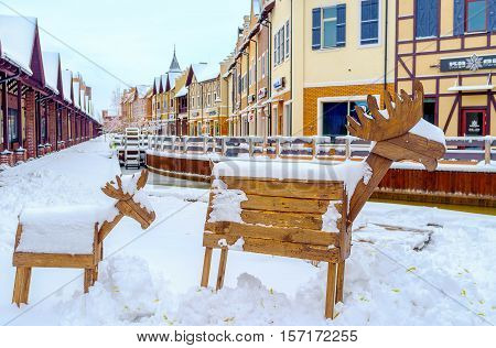 KIEV UKRAINE - NOVEMBER 11 2016: The wooden moose covered with snow in Dutch Revival style shopping neighborhood with the water wheel in a canal on background on November 11 in Kiev.