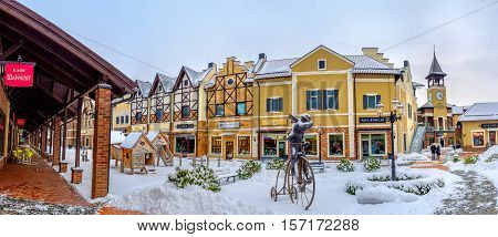 KIEV UKRAINE - NOVEMBER 11 2016: Panorama of the Dutch Revival outlet city decorated with the clock tower parks and the statue of a man riding the vintage cycle on November 11 in Kiev.