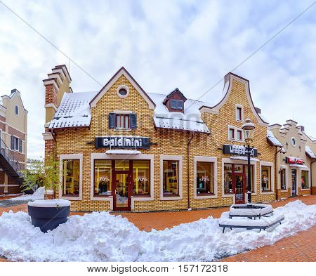 KIEV UKRAINE - NOVEMBER 11 2016: The boutiques of the Dutch style outlet city covered with snow and prepare for holiday sales on November 11 in Kiev.