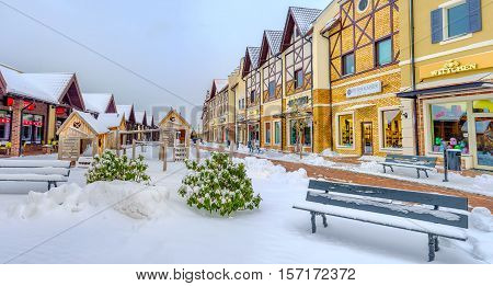KIEV UKRAINE - NOVEMBER 11 2016: The gambrel-roofed houses of the Dutch shopping neighborhood with the snowy benches on the foreground on November 11 in Kiev.