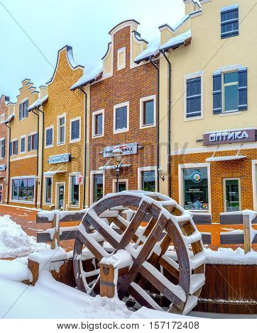 KIEV UKRAINE - NOVEMBER 11 2016: The Dutch style gambrel houses of the shopping neighborhood with the snowy wooden water wheel on the foreground on November 11 in Kiev.