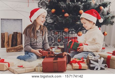 Cute happy excited children, boy and girl in santa hats unwrap christmas present box in beautiful room. Sister and brother open Xmas gifts near decorated tree and fireplace. Family holiday