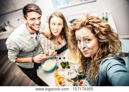Group of friends having dinner home and fun together