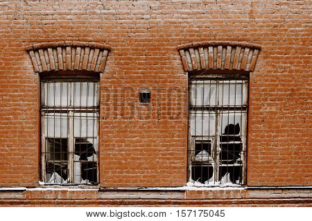 Two broken windows of old plant. Windows with broken glass on the old red wall