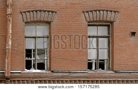 Two broken glass windows of Old residential building in abandoned condition
