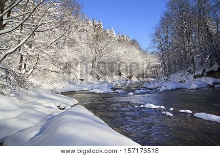 River bend in winter forest with a lot of snow