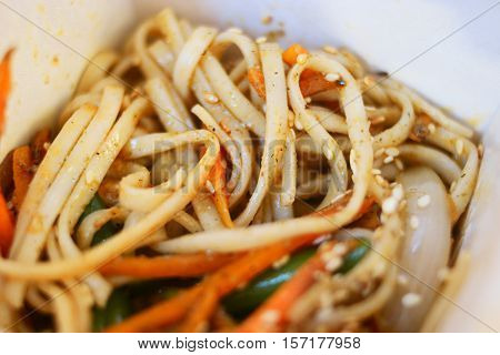 Asian fast food. fryed noodles in open take away cardboard box above view.