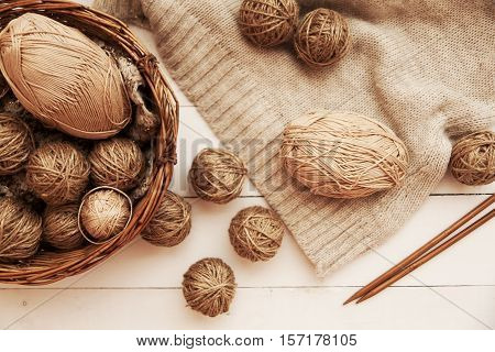 Beige yarn in balls lies on the table and braided basket near needles and yarn